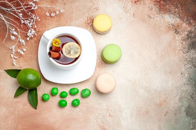 Vue de dessus tasse de thé avec des bonbons et des macarons sur une table lumineuse biscuit au citron et au thé