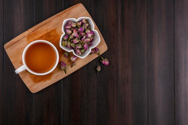 Vue de dessus de la tasse de thé avec des boutons de rose séchés sur tableau noir sur une surface en bois