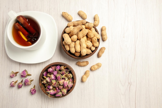 Vue de dessus tasse de thé avec des cacahuètes et des fleurs sur un goûter de fleur de thé de noix de bureau blanc