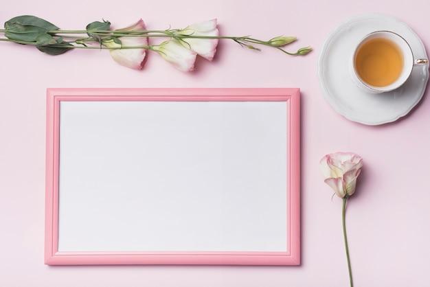 Une vue de dessus d'une tasse de thé avec un cadre photo et des fleurs d'eustoma sur fond rose