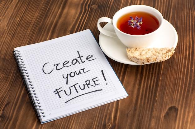 Vue de dessus tasse de thé avec cahier sur bureau marron