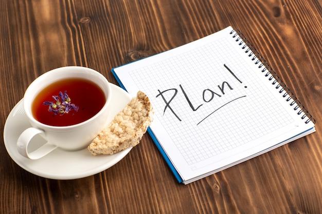 Vue de dessus tasse de thé avec cahier sur la surface rustique brune
