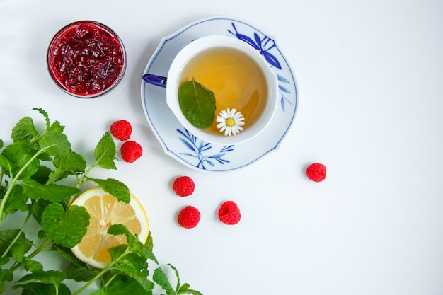 Vue de dessus une tasse de thé à la camomille au citron, feuilles de menthe, framboises, confiture en soucoupe sur tissu