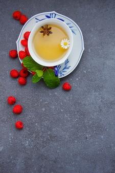 Vue de dessus une tasse de thé à la camomille avec des feuilles de menthe et de framboise dans une soucoupe.