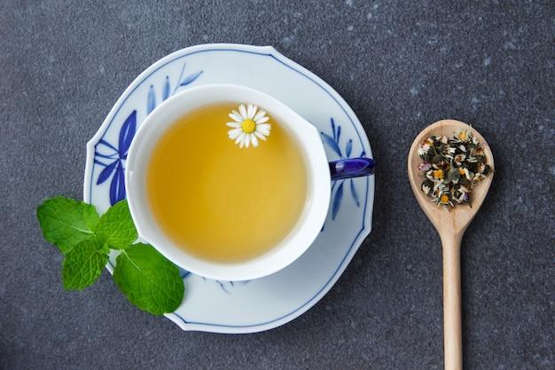 Vue de dessus une tasse de thé à la camomille avec des feuilles de menthe et des herbes de camomille dans une cuillère.