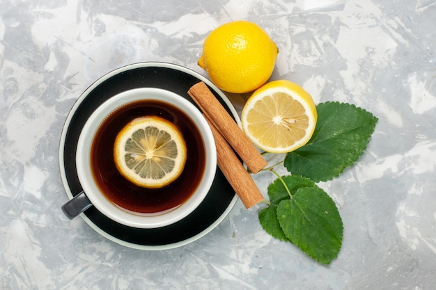 Vue de dessus tasse de thé à la cannelle et au citron sur la surface blanc clair