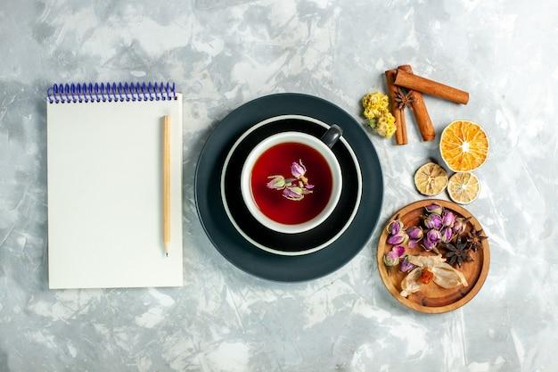 Vue de dessus tasse de thé avec de la cannelle et des fleurs sur un bureau blanc thé fleur de boisson sucrée