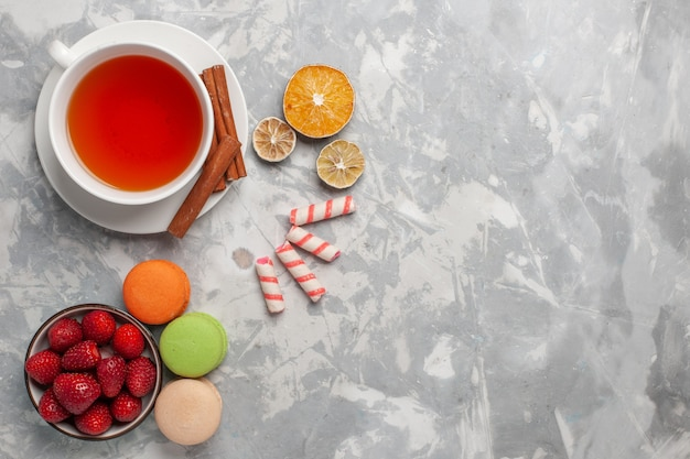 Vue de dessus tasse de thé à la cannelle et macarons français sur un bureau blanc