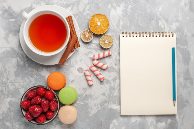 Vue de dessus tasse de thé à la cannelle et macarons français sur surface blanche