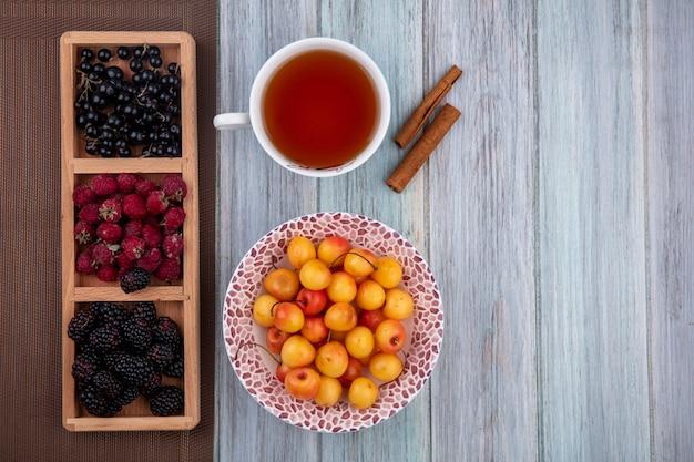 Vue de dessus de la tasse de thé avec des cerises blanches vif, cassis, framboises et mûres sur un support sur une surface grise