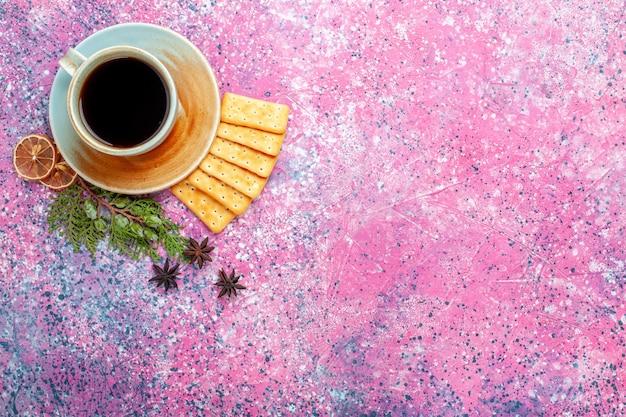 Vue de dessus tasse de thé avec des craquelins sur le bureau rose