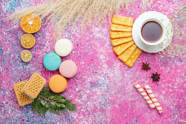 Vue de dessus tasse de thé avec des craquelins et des macarons français sur le bureau rose clair