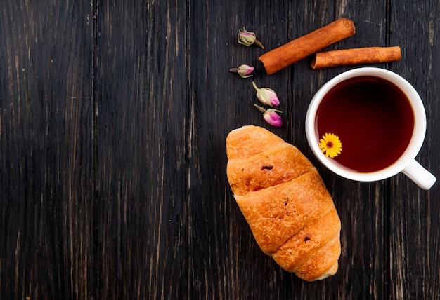 Vue de dessus d'une tasse de thé avec croissant et bâtons de cannelle sur bois noir avec copie espace