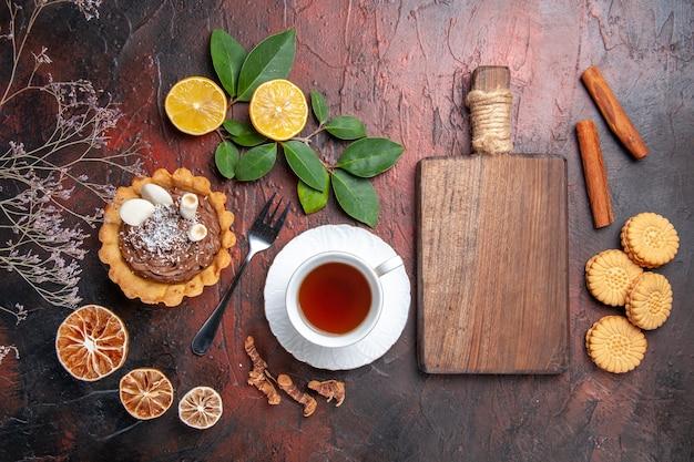 Vue de dessus tasse de thé avec un délicieux petit gâteau sur le biscuit de biscuit de dessert de plancher sombre