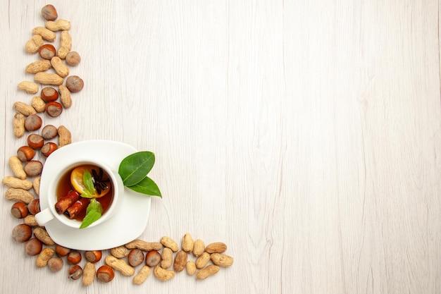 Vue De Dessus Tasse De Thé Avec Différentes Noix Sur Un Bureau Blanc Couleur Thé Fruits Cérémonie Noix Photo gratuit