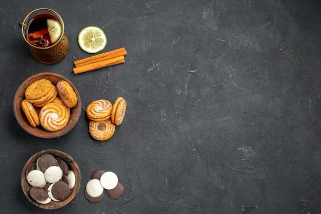 Vue de dessus tasse de thé avec différents cookies sur une surface sombre