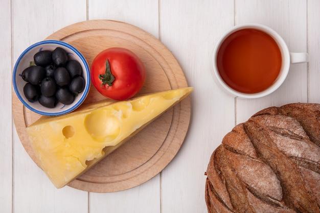 Vue de dessus tasse de thé avec du fromage tomate olives sur un support et une miche de pain noir sur fond blanc