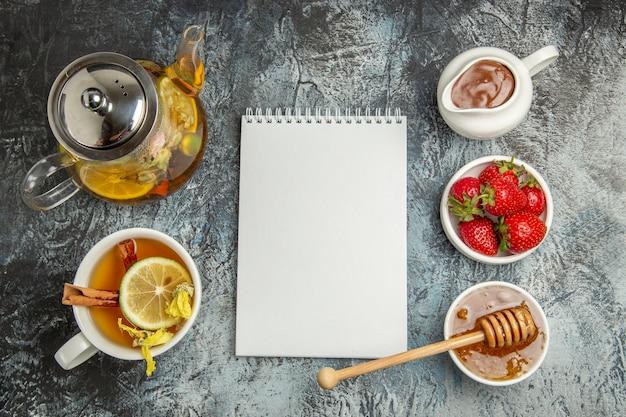 Vue de dessus tasse de thé avec du miel et des fruits sur une surface légère thé aux fruits sucrés