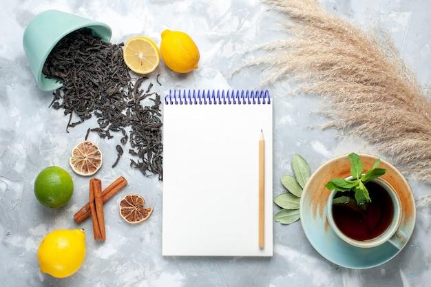 Vue de dessus tasse de thé avec du thé séché au citron et du bloc-notes à la cannelle sur table lumineuse, thé aux grains d'agrumes de couleur sèche