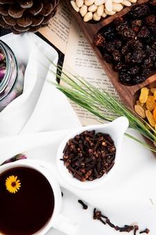 Vue de dessus d'une tasse de thé avec des épices de clou de girofle dans un bol et des noix mélangées et des fruits secs dans une boîte en bois sur les pages du livre