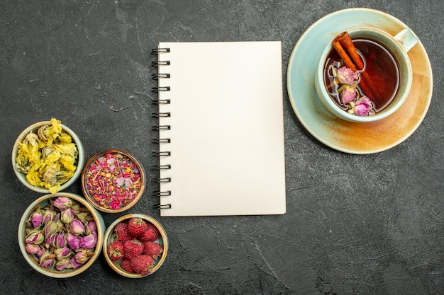 Vue de dessus tasse de thé avec des fleurs sur la fleur de cérémonie du thé de bureau gris