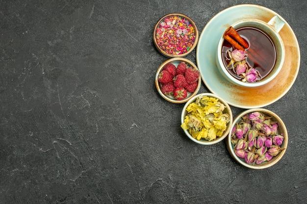 Vue de dessus tasse de thé avec des fleurs et des framboises sur la fleur de saveur de boisson aux fruits de thé de fond sombre