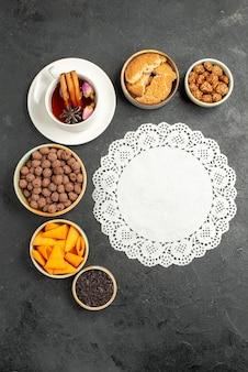 Vue de dessus tasse de thé avec des flocons et des noix sur une surface grise de couleur bonbon au thé