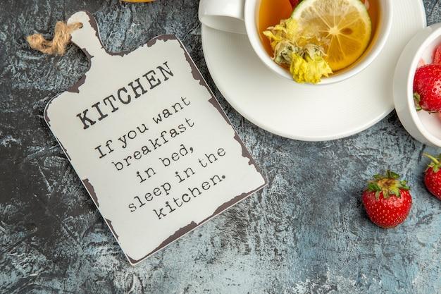 Vue de dessus tasse de thé avec des fraises et un bureau drôle sur la surface sombre de la baie de thé aux fruits