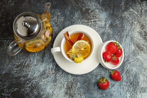 Vue de dessus tasse de thé avec des fraises sur la surface sombre fruits baies de thé