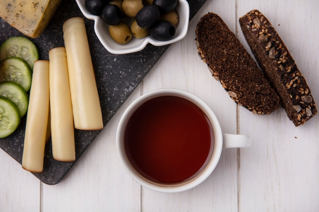Vue de dessus tasse de thé avec des fromages fumés aux olives et tranches de pain noir sur fond blanc