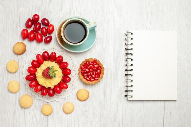 Vue de dessus tasse de thé avec un gâteau crémeux et des fruits sur un bureau blanc
