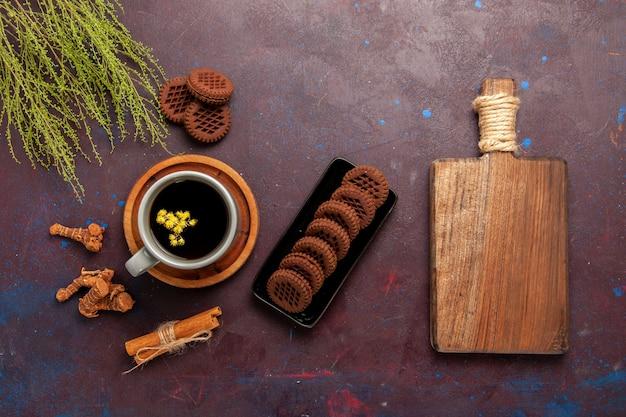 Vue de dessus tasse de thé à l'intérieur de la plaque et tasse sur fond sombre boisson thé couleur photo douce