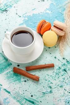 Vue de dessus tasse de thé avec des macarons et de la cannelle sur une surface bleue