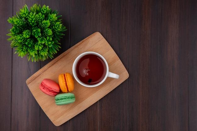 Vue de dessus d'une tasse de thé avec des macarons colorés sur une planche à découper sur une surface en bois