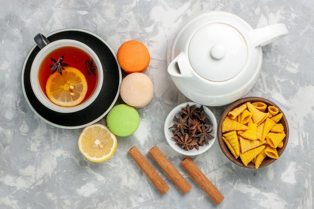 Vue de dessus tasse de thé avec des macarons français et de la cannelle sur une surface blanche