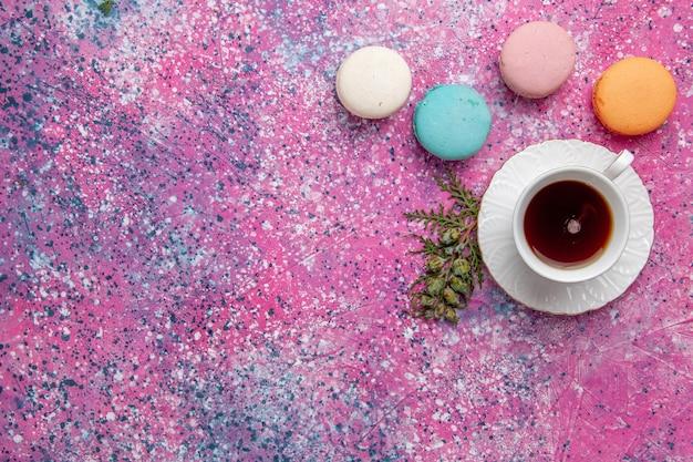 Vue de dessus tasse de thé avec des macarons français colorés sur le gâteau mural rose clair biscuit sucre tarte sucrée thé