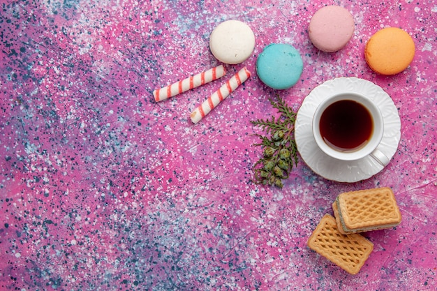 Vue de dessus tasse de thé avec macarons français colorés et gaufres sur le gâteau rose gâteau biscuit sucre tarte sucrée thé