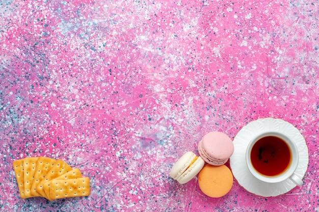Vue de dessus tasse de thé avec des macarons français et des craquelins sur le bureau rose