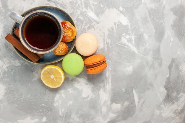 Vue de dessus tasse de thé avec des macarons sur une surface blanche