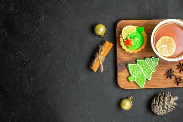 Vue de dessus d'une tasse de thé noir avec des accessoires de nouvel an au citron, cône de conifère et citrons verts à la cannelle sur fond noir