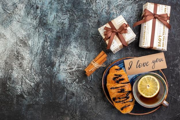 Vue de dessus d'une tasse de thé noir délicieux croissant je t'aime écrivant sur un plateau de cadeaux de limes à la cannelle sur fond sombre