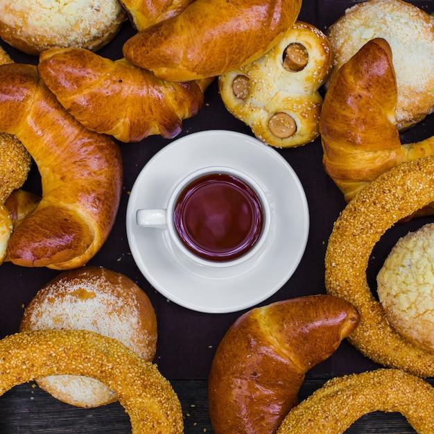 Vue de dessus d'une tasse de thé noire entourée de hot dogs, simit et petits pains