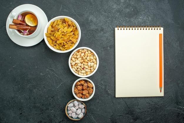Vue de dessus tasse de thé avec noix et raisins secs sur une surface sombre thé sucré aux noix
