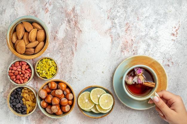Vue de dessus tasse de thé avec des noix de raisins secs et des tranches de citron sur une surface blanche thé aux fruits boisson aux agrumes