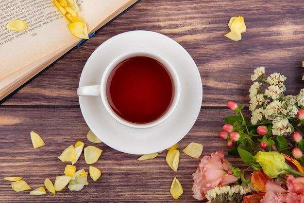 Vue de dessus d'une tasse de thé avec des pétales jaunes de fleurs sur bois