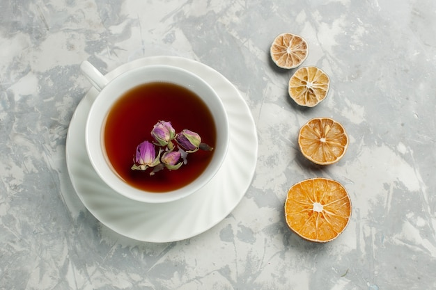Vue de dessus tasse de thé avec petites fleurs et citron sur un bureau blanc