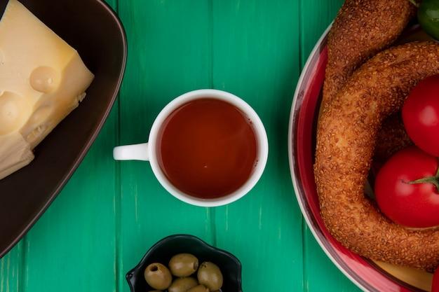 Vue de dessus d'une tasse de thé avec des petits pains sur une assiette avec des olives sur un bol sur un fond en bois vert