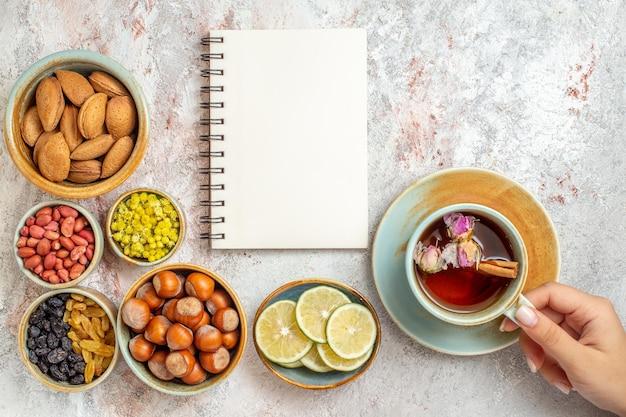 Vue de dessus tasse de thé avec des raisins secs, des noix et des tranches de citron sur une surface blanche, thé aux fruits, boisson aux agrumes