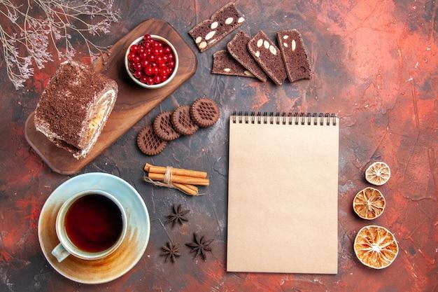 Vue de dessus de la tasse de thé avec rouleau de biscuit sur une surface sombre