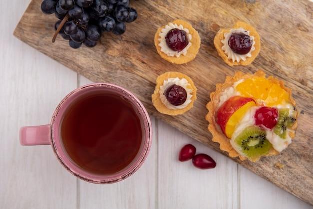 Vue de dessus tasse de thé avec tartelettes et raisins noirs sur une planche à découper